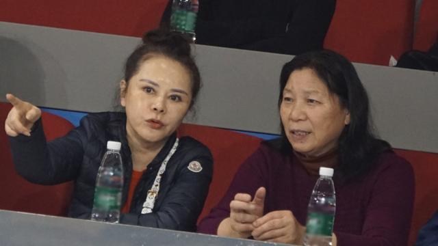 孙莉的妈妈在球场上观看了比赛。她的皮肤娇嫩有光泽,不像60多岁的老太太